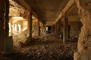 A hallway that was once walked by doctors and nurses is left shattered by the weapons of the Israeli military. The hospital in Quneitra demonstrates the aggression employed by the Israeli forces before returning control of the vicinity. Twisted, rusted pipes are strewn throughout the massive piles of rubble. From the outside the building looks torn, but the real destruction emanates from within the bullet-ridden rooms and deteriorating walls.